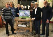 Vrijwilligeres en wethouder Piet de Klein tonen cheque in Reparatiecafe Beuningen